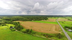 Aerial footage. Flight over a green grassy fields. Beautiful massive clouds. Stock Footage