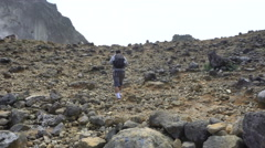 Young man backpacker hiking rocky slope of active Sibayak volcano Stock Footage