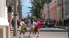 School children congregate on a busy corner in the  Cuban town of Cienfuegos. Stock Footage