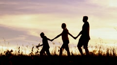 Happy family of mother, father and little child  walking outside holding hands Stock Footage