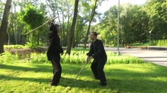 Qigong. Exercise with a wooden stick. Two men practicing elements of qigong. 4K Stock Footage