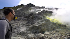 Young man in respirator mask looking at fumaroles on active Sibayak volcano Stock Footage