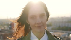 Close-up. young woman standing on the roof at sunset turns the head and her hair Stock Footage