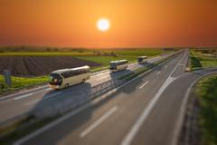 Tilt shift image of fast travel buses on the highway at sunset Stock Photos