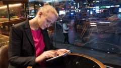 Time lapse shot of woman sitting in cafe using touch pad on the city background Stock Footage