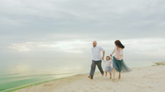 Steadicam slow motion shot: Family fun. Mom dad and daughter run on the beach Stock Footage