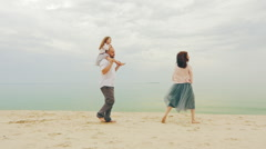 Happy family of three people walking along the sea. Against the background of Stock Footage