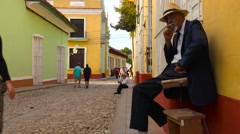 A cuban man smokes a cigar on the colorful streets of Trinidad, Cuba. Stock Footage