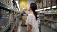 Asian girl, woman walking, looking and shopping in supermarket isle Stock Footage