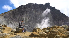 Young man using tablet at active Sibayak volcano, North Sumatra, Indonesia Stock Footage