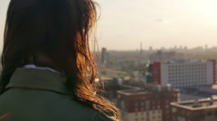 Back view. Wind blows long hair beautiful young women. girl standing on the roof Stock Footage