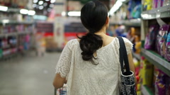 Asian girl, woman walking, looking and shopping snacks in supermarket isle Stock Footage