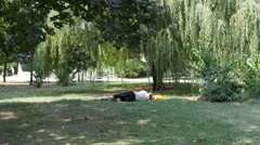 Homeless tramp vagabond man sleeping on the lawn in the park Stock Footage