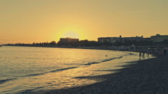 Sunset on the beach in the area tourists. The waves of the sea easily descend to Stock Footage