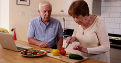 4k, Happy senior couples cutting vegitables in their kitchen Stock Footage
