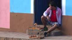A man sits on the street with his pet bird in a cage and watches the world go Stock Footage