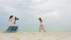 Young mother a photographer trying to take a picture of her daughter on the Stock Footage