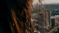 Wind blows long dark hair. girl standing on the roof with his head down Stock Footage