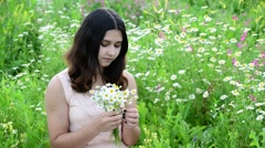 Beautiful girl with bouquet of daisies in a meadow Stock Footage