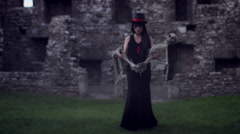 4k Halloween Shot of a Witch Walking with a Skeleton and Dropping it Stock Footage