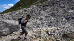 Young man backpacker hiking rocky slope of Sibayak volcano to smoking fumaroles Stock Footage