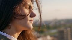 Wind blows long dark hair. girl standing on the roof with his head down. close Stock Footage
