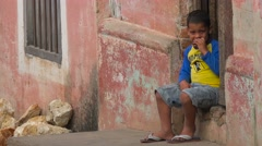 A little boy sits on the street watching passersby in Trinidad, Cuba. Stock Footage