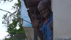 A friendly old man waves, gives the thumbs up and smiles in Trinidad, Cuba. Stock Footage
