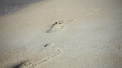Foaming Sea Waves Wash away Footprints on a Beach Sand. Slow Motion Stock Footage