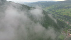 Drone flying in the clouds above a mountain village Stock Footage