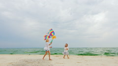 Two children playing with a kite on the beach on sea and sky background Stock Footage