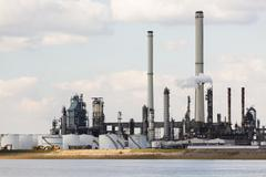 A large oil refinery with smoke stacks in the port of Antwerp, Belgium with l Stock Photos