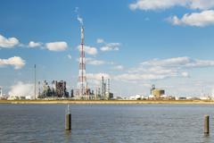 A refinery with tall flare stack in the port of Antwerp, Belgium with lots of Stock Photos