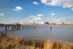 Long exposure shot of a large refinery with gas storage tanks in the port of  Stock Photos