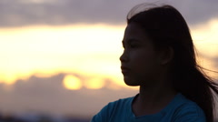 Silhouette of woman looking up at sunset sky with wind blowing hair, Slow motion Stock Footage