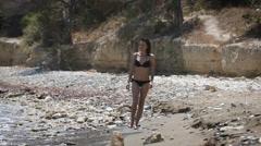 A beautiful woman walking at a beach wearing black bikini Stock Footage