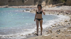 Beach vacation. Beautiful woman in the black bikini enjoying perfect sunny day Stock Footage
