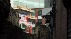 Chinese archway entrance to chinatown with old castle wall in foreground Stock Footage
