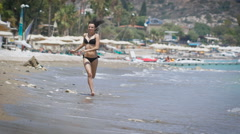 A beautiful young woman running at a beach in Cyprus Stock Footage