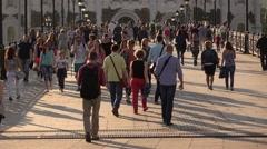 People go on wide sunlit pedestrian footbridge in downtown, slow motion Stock Footage