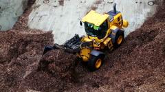 Volvo buldozzer dicharging wood chips Port of Stockholm Sweden June 2016 Stock Footage