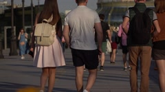 Group of friends walk together on sunlight promenade, slow motion Stock Footage