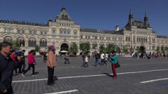 Elderly asian tourist couple pose and make pics on red square, slow motion Stock Footage