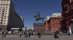 People sit around Marshal Zhukov monument near Historical Museum, tracking shot Stock Footage