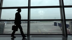 Bored looking business man silhouette, pace against glass wall terminal window Stock Footage