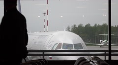 Passenger airliner seen through terminal window, begin move back, man silhouette Stock Footage