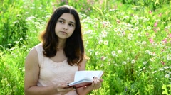 Dark-haired girl reading a book on nature Stock Footage