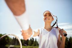 Young female tennis player greets with trainer. Stock Photos
