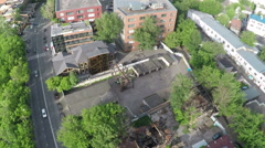 Aerial shot of street with car traffic and ruined house Stock Footage