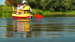 Family traveling in kayak along the river Stock Footage